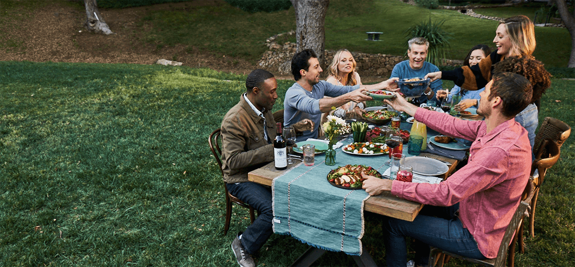 A group of people sitting outdoors around a picnic bench sharing Atkins meals