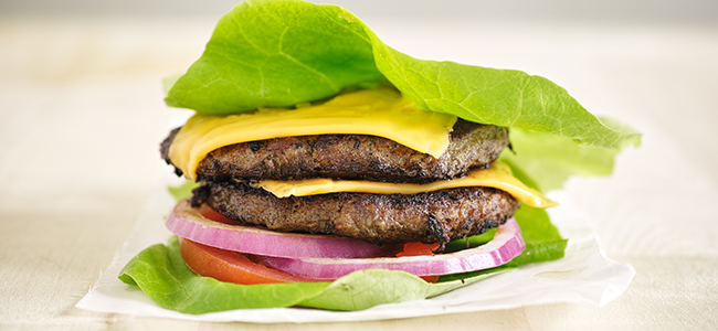 Burger patties with cheese, tomatoes, and red onion wrapped in lettuce.