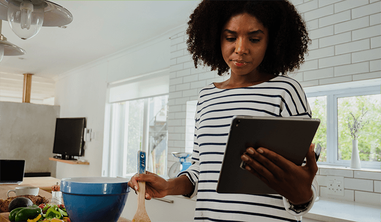 A Black woman with natural hair and a striped shirt reads on a tablet with a skeptical look on her face while cooking.