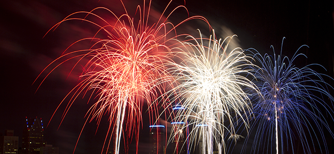 Red, white, and blue fireworks in the night sky.