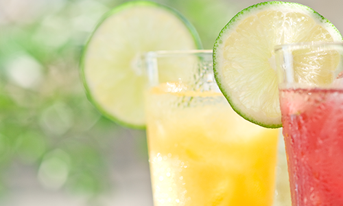 Two refreshing ice-cold beverages with a slice of lime