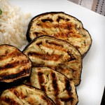Slices of grilled eggplant on a plate next to rice
