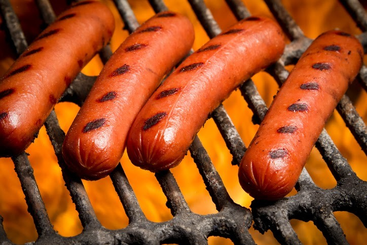 Four hot dogs with grill marks on the grill