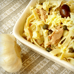 Pasta salad with tuna, capers, and lemon in a dish with a bulb of garlic beside it