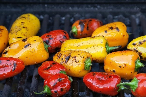 Colorful little roasted peppers on the grill