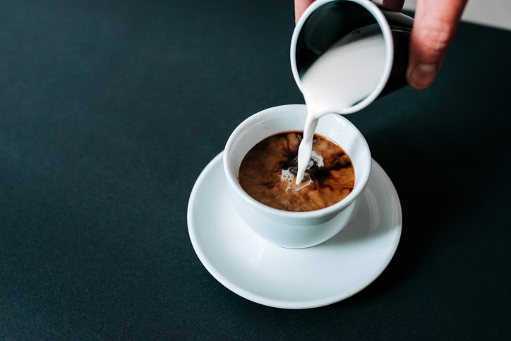 pouring cream into cup of coffee
